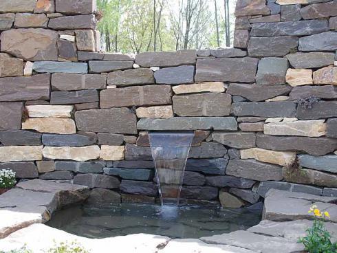 Foto: BGL. - Oft dienen Trockenmauern als Grundstückgrenze, ähnlich der traditionellen Verwendung auf Wiesen und Feldern. Ein in die Mauer eingelassener Brunnen, der munter plätschert, schafft zusätzlich eine erfrischende Atmosphäre.