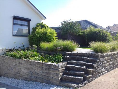 Foto BGL: Steine im Vorgarten können von ganz praktischem Nutzen sein. Liegt das Grundstück am Hang, kann zum Beispiel mit einer Natursteinmauer und integrierter Treppe eine gerade Fläche modelliert werden.