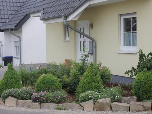 Foto BGL: Steine können auch bewusst an wenigen Stellen als Blickfang positioniert werden - beispielsweise als natürlich anmutende Grundstücksbegrenzung. Entlang der Hausmauer wird Kies dagegen häufig als Spritzschutzstreifen eingesetzt.