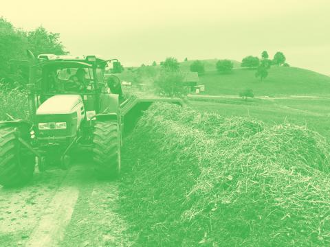 Traktor mit Wender fährt einer Kompostmiete entlang.